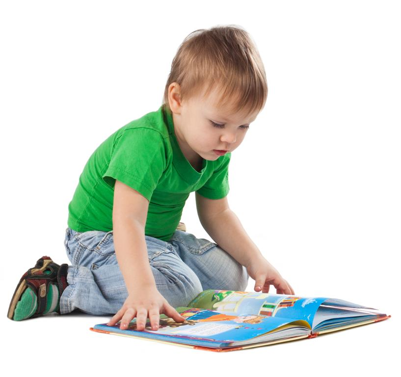 Enthusiastic little boy with a book sitting on the floor, isolated on white