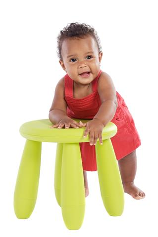 Toddler playing with a chair a over white background